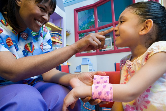 pediatric nurse working closely with young patient